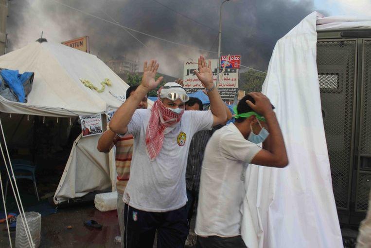 Demonstranten houden hun handen omhoog bij een van de tentenkampen. Beeld ap