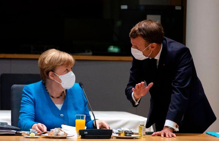 De Duitse bondskanselier Angela Merkel in gesprek met de Franse president Emmanuel Macron voorafgaand aan de tweede dag van het EU-overleg over de vorming van een Europees herstelfonds voor de coronacrisis. Beeld AFP