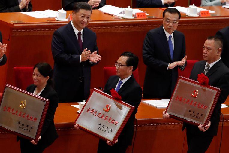 De Chinese leiders Xi Jinping (L) Li Keqiang (R) applaudisseren voor zojuist onderscheiden 'Covid-19-strijders'.   Beeld EPA