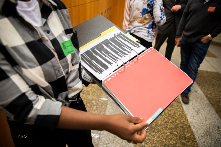 Gedupeerden in de affaire rond kinderopvangtoeslag tonen hun zwartgelakte dossiers. Een deel van de ouders namen de dossiers mee naar de Tweede Kamer voor het debat met Menno Snel.  Beeld ANP