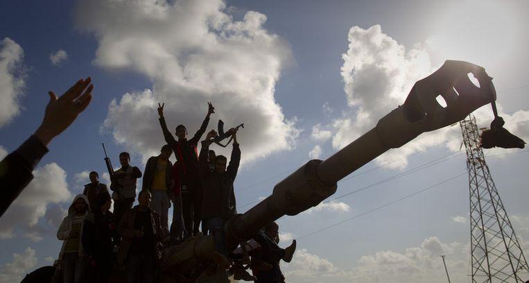 Blije opstandelingen op een tank die van de troepen van Kadhafi is geweest. Beeld ap