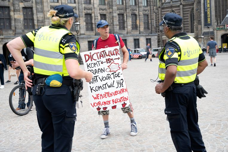 Ook in Amsterdam werd volop geprotesteerd. Hier wordt op de Dam een demonstrant tegen het coronabeleid aangesproken door de politie. Beeld Hollandse Hoogte /  ANP