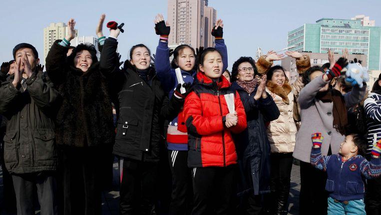 Noord-Koreanen vieren het nieuws over de atoomproef op het plein voor het station van Pyongyang. Op een groot scherm wordt het nieuws getoond. Beeld ap