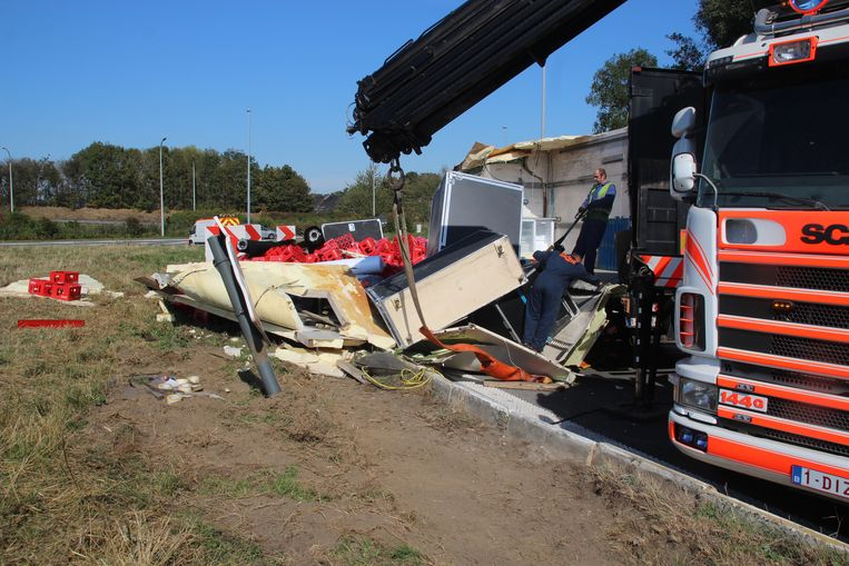 Tijdens het recht trekken van de vrachtwagen scheurde de zijkant open en kwamen honderden bakken frisdrank op de grasberm terecht.