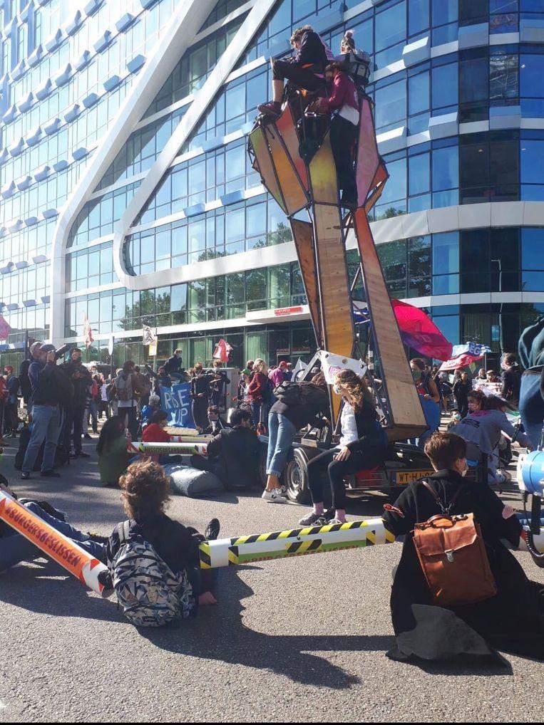 Demonstranten zitten op de weg en aan elkaar vastgeketend met extra lange lockons om 1,5 meter afstand te houden. Beeld Bart van Zoelen