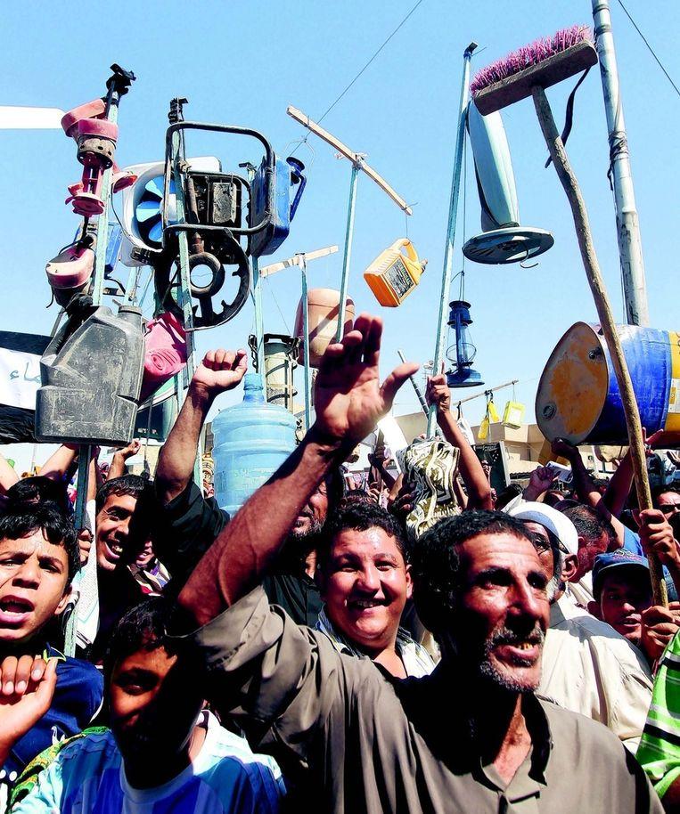 Aanhangers van de radicale sjiitische geestelijke Al-Sadr demonstreren in Bagdad tegen de Amerikaanse aanwezigheid in Irak, en voor betere openbare voorzieningen. FOTO © AFP Beeld
