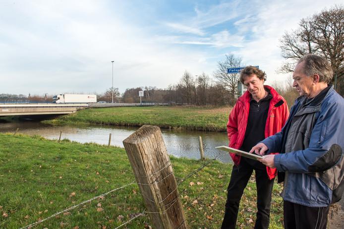 Eerder dit jaar: Ton Kroes (links) en Sjef Langeveld van Vereniging Markdal bij het viaduct van de A58 over de Mark. Ze willen de snelweg onder het water door hebben.