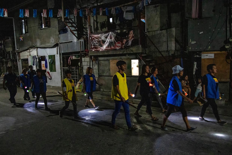 Moeders en grootmoeders patrouilleren 's avonds in de wijk Santa Ana in de Filipijnse hoofdstad Manilla, onder hen één jongen Jericho Semana