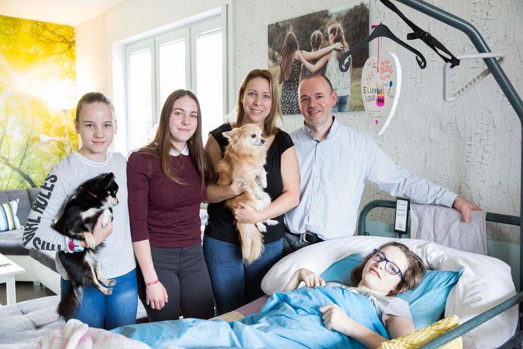 Sharon in haar ziekenbedje, samen met haar mama Verena en papa Yve en haar zusjes Ashley en Lisa met de hondjes Lola en Bibber.