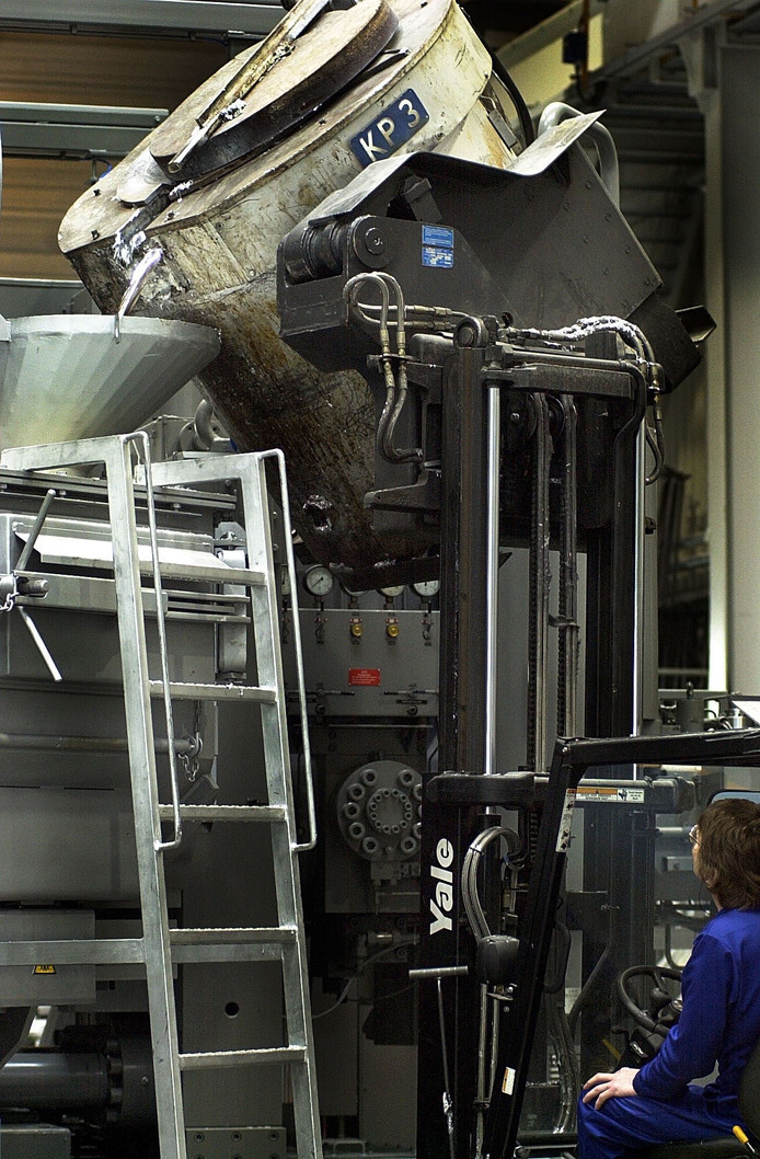 Het vullen van de gietmachine bij Alucast.
