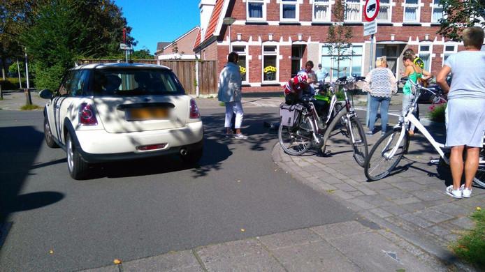 Het slachtoffer wordt ter plekke aan zijn verwondingen behandeld. De witte auto op de foto was niet bij het ongeluk betrokken. Foto: GinoPress B.V.