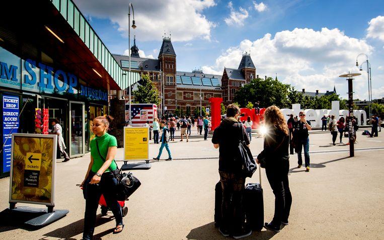 Toeristen met rolkoffers op het Museumplein in Amsterdam. Beeld ANP