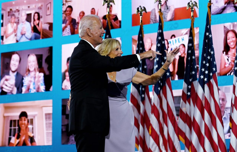 Joe Biden en zijn vrouw Jill zwaaien naar hun digitaal aanwezige supporters op de laatste dag van de Democratische Conventie.  Beeld  Olivier Douliery / AFP