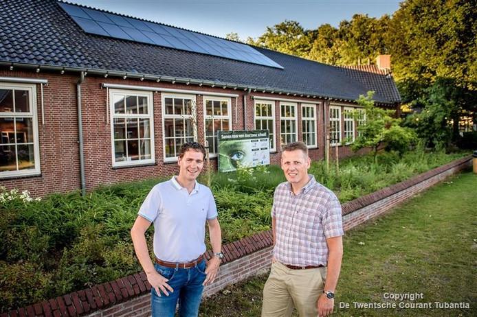 Bas Rikhof (links) en Edwin de Veen van de werkgroep Duurzaam Geesteren bij de zonnecollectoren van de Aloysiusschool.