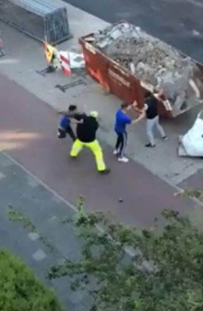 Flatbewoners filmen hoe de verkeersregelaar in elkaar wordt geslagen. De beelden verschenen op Dumpert. De man in het blauwe shirt en witte schoenen probeert de vechtersbazen tegen te houden, maar kan niet voorkomen dat de man in grijze trainingsbroek een steen uit de container pakt.