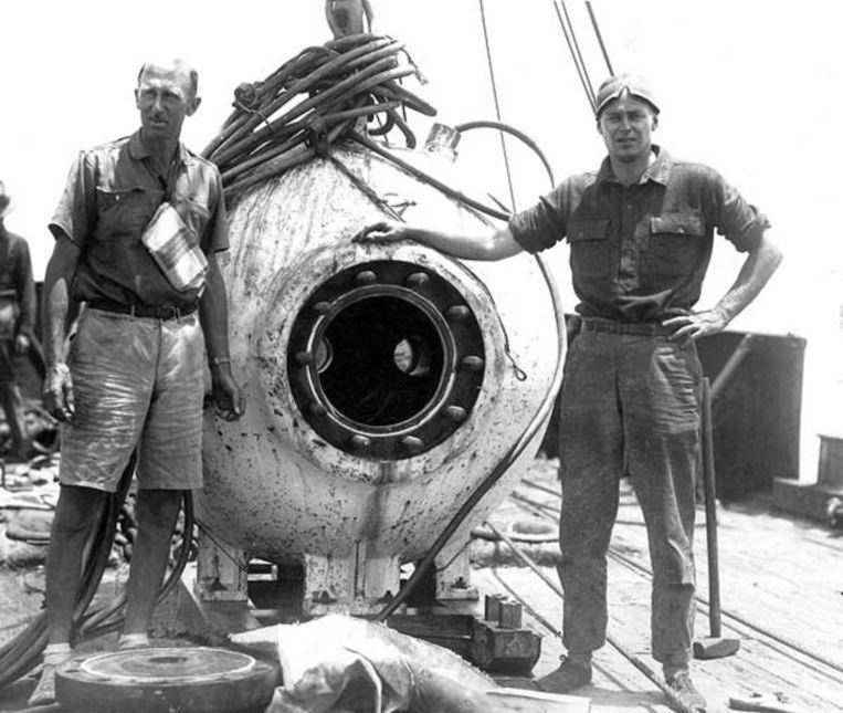 Beebe (links) met de stalen bol waarin hij de diepzee verkende. Beeld Wikimedia, U.S. Federal Government (National Oceanic and Atmospheric Administration)