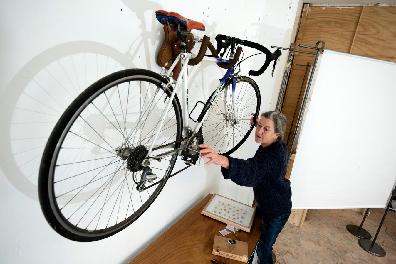 Els Bugter hangt de fiets van Kenny van Hummel recht. Het hangt op het gewei van een zadel en fietsstuur van Jasper Bugter.