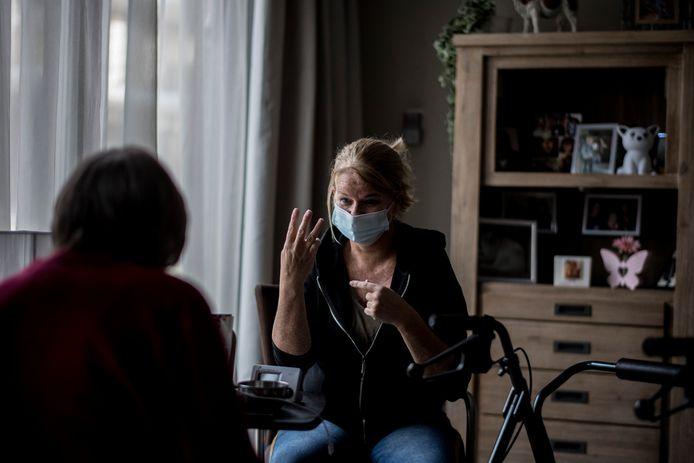 Doventolk Silvia Hartzeman (zelf ook doof) werkzaam bij De Gelderhorst in gesprek met 1 van haar clienten. Vanwege de mondkapjesplicht is het lastig werken zo. Liplezen gaat niet.