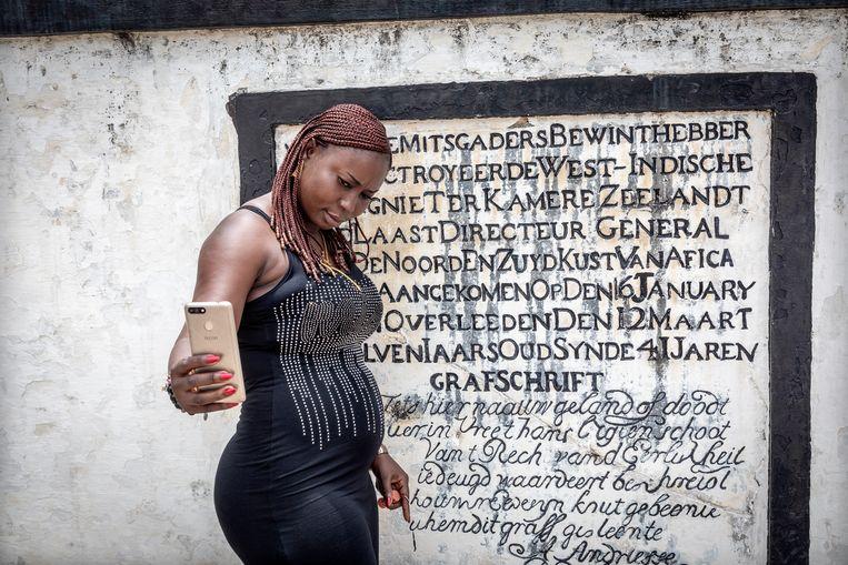 Ghanese bezoekers maken selfies en foto's op de trappen en naast het grafschrift van een van de Nederlandse bewindvoerders van Fort Elmina, gebouwd door de Portugezen, en daarna veroverd door de Nederlanders die van hieruit bijna 250 jaar lang handel dreven en slaven verscheepten naar de plantages in Zuid Amerika en het Caribische gebied. Beeld Sven Torfinn