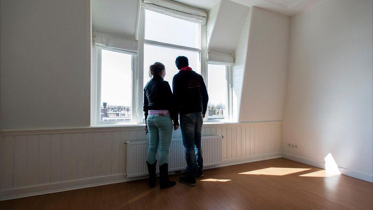 Een woningzoekend stel kijkt uit het raam van een leegstaande woning tijdens de landelijke Open Huizen Dag. Beeld anp