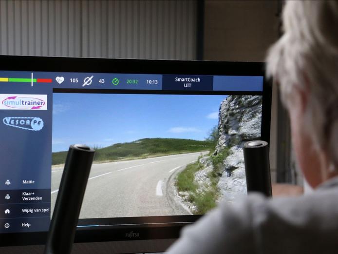 Een parkinsonpatiënt fietst op een hometrainer tegen een virtuele tegenstander.