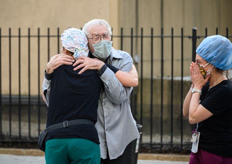 Een verpleegster omhelst voor een ziekenhuis in New York een patiënt die genas van Covid-19 in New York terwijl een emotionele collega-verpleegster toekijkt.