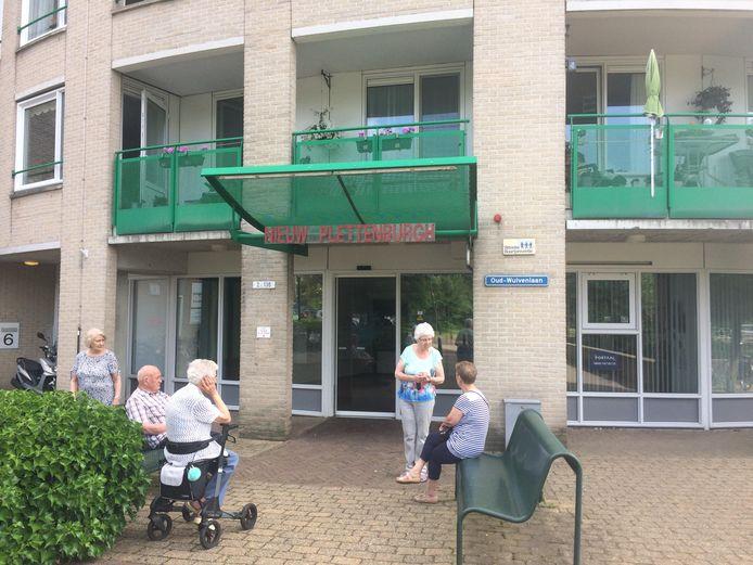 Bewoners van seniorenflat Nieuw Plettenburgh maken een praatje voor de entree van hun gebouw. 's Avonds blijven ze binnen, want dan vinden ze de straat te onveilig.