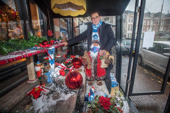 Patrick van Aller van café-restaurant Van Kinsbergen op het Prins Hendrikplein bij zijn kersthuisje dat twee weken geleden al aan gruzelementen ging en de vernielingen in de buurt houden niet op. 'Waar blijven de handhavers en de camera's?!'
