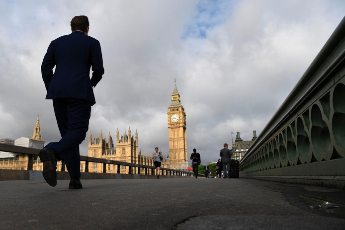 Morning commuters cross Westminster Bridge with Elizabeth Tower (Big Ben) and the Houses of Parliament in the background in central London on June 9, 2017 after results in a snap general election show a hung parliament with Labour gains and the loss of the Conservative majority. British Prime Minister Theresa May faced pressure to resign on Friday after losing her parliamentary majority, plunging the country into uncertainty as Brexit talks loom. The pound fell sharply amid fears the Conservative leader will be unable to form a government and could even be forced out of office after a troubled campaign overshadowed by two terror attacks. / AFP PHOTO / Paul ELLIS