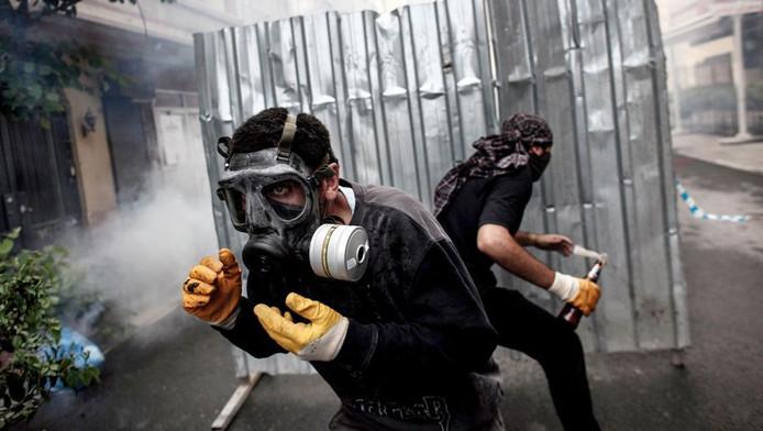 Demonstranten met gasmaskers duiken weg achter hun barricades.