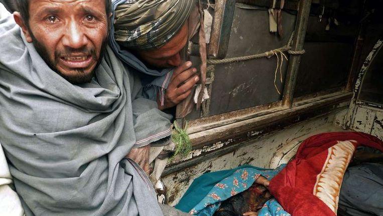 Een Afghaan staat naast de lichamen van de neergeschoten burgers. Beeld null