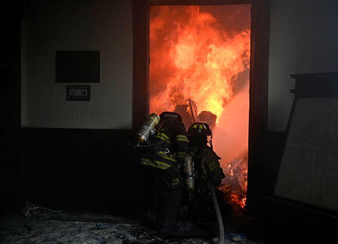 Brandweerlieden proberen het vuur te blussen.