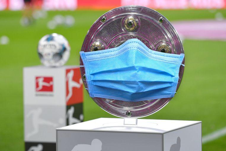 De Duitse kampioensschaal met een mondmasker. Vanaf half mei is de titelstrijd weer geopend. Beeld BSR Agency