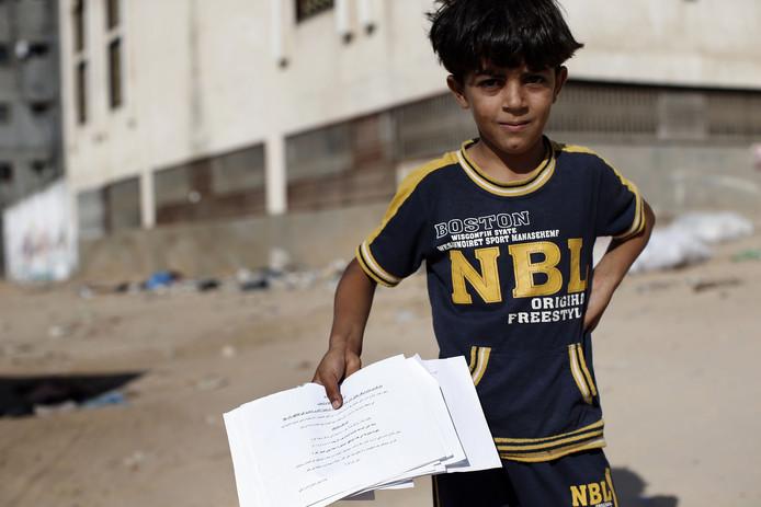 Un jeune Palestinien tient un tract israélien appelant à l'évacuation.