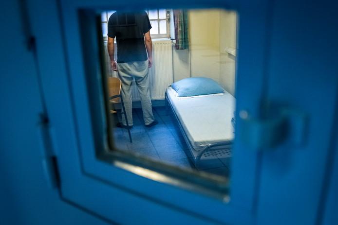 Een man kijkt uit het raam van een cel in een gevangenis.