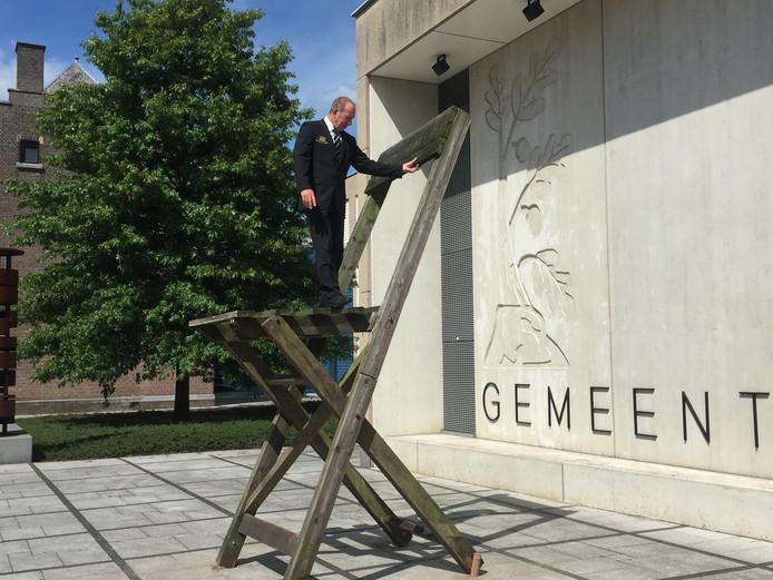 Gemeentebode van Bergeijk, Henri Wuijts, inspecteert de megastoel op het plein voor het gemeentehuis van Bergeijk.