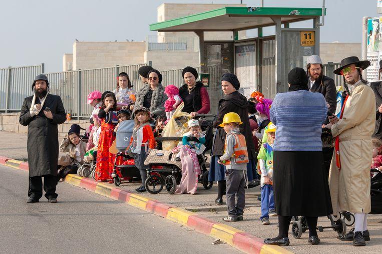 Haredi-joden wachten op de bus in Beit Shemesh. Beeld Geert van Kesteren