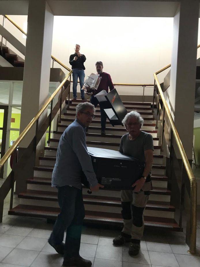 Twee mannen dragen de zware digitale filmprojector naar beneden.