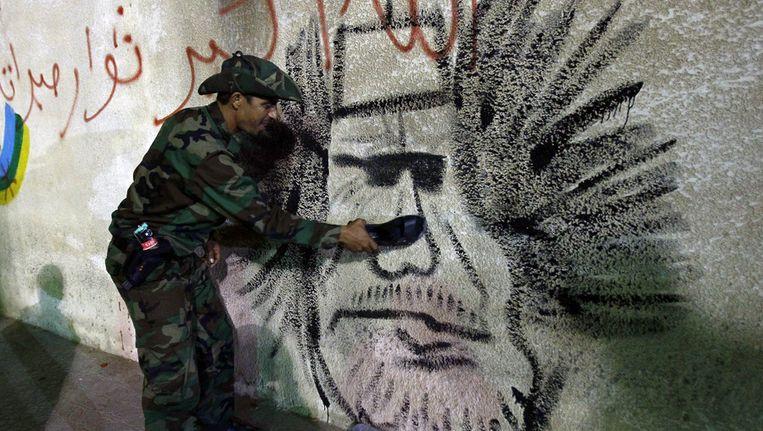 Een opstandeling slaat met een schoen tegen een grafitti-afbeelding van Moammar Kaddafi. Beeld ap