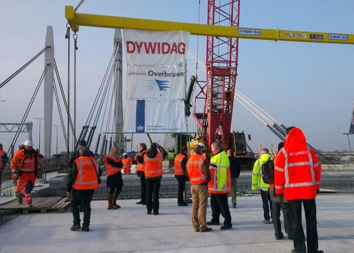 Medewerkers van Rijkswaterstaat donderdagochtend bezig met het plaatsen van de laatste ligger op de brug.