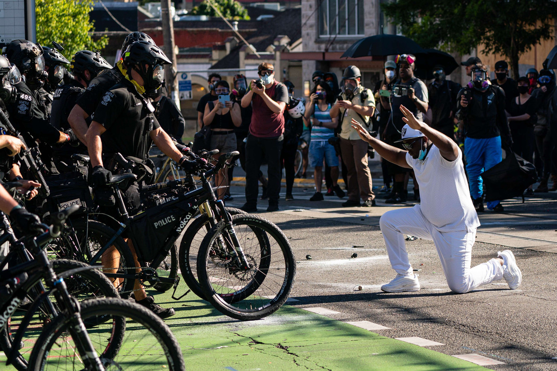 Een demonstrant knielt voor de politie tijdens het protest in Seattle