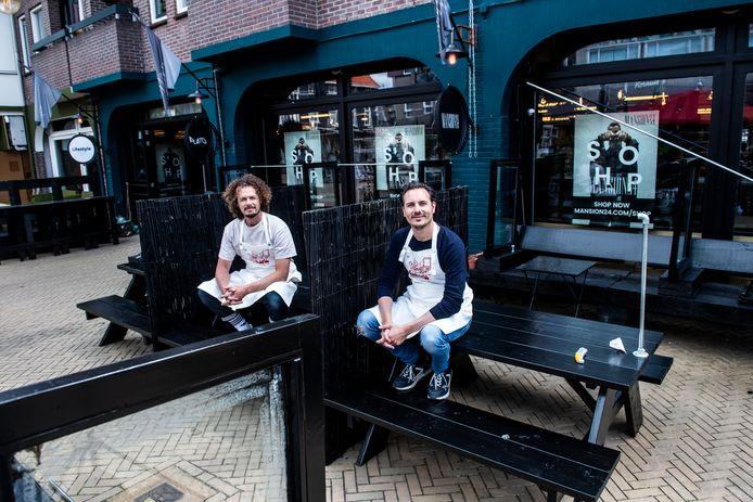 Robin Batens (l) en Simon Giaccotto op het terras van Mansion24 dat met kozijnen en afscheidingen zo corona-proof mogelijk is gemaakt. Vanaf maandag zijn er pizza's te koop.