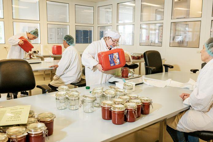Ketchup wordt overgegoten in een sociale werkplaats in Schiedam, waar medewerkers de producten inpakken.