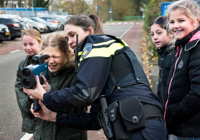 Samen met de politie voeren basisschoolleerlingen een snelheidscontrole uit met een lasergun op de Fazantenkamp.