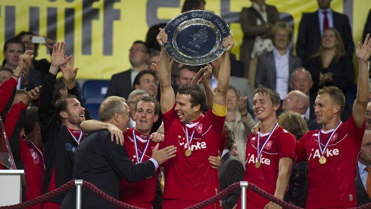 FC Twente heeft in de Arena de wedstrijd tegen Ajax om de Johan Cruijff Schaal 2011 gewonnen. FC Twente won met 2-1 van Ajax. Oud-speler Eddy Achterberg reikt de schaal uit aan aanvoerder Peter Wisgerhof. ©ANP Beeld