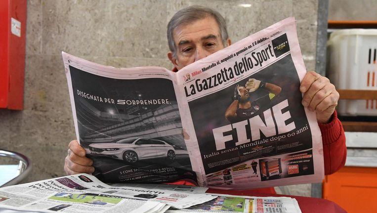 Een man leest over de eliminatie van het Italiaanse voetbalteam. Beeld ANP