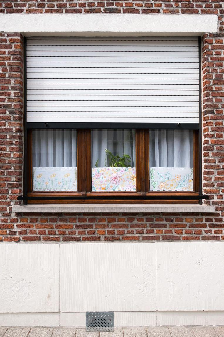 De slachtoffers hebben nu tekeningen van bloemen voor het raam geplaatst.