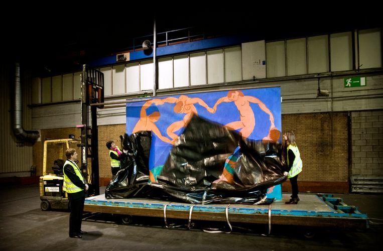 Een kist met daarin het schilderij 'De dans van Henri Matisse' wordt maandag ontdaan van zijn reisverpakking op Schiphol, 2010. Beeld ANP
