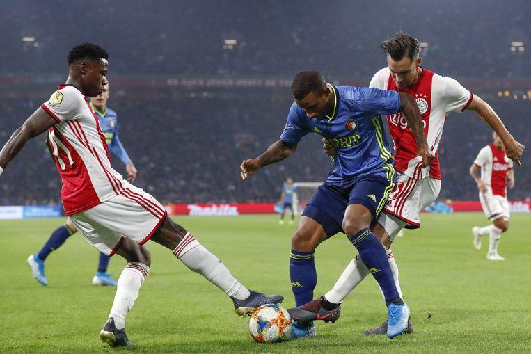 Luciano Narsingh (midden) van Feyenoord in duel met Ajax-spelers Nico Tagliafico (rechts) en Quincy Promes (links)  Beeld ANP Sport