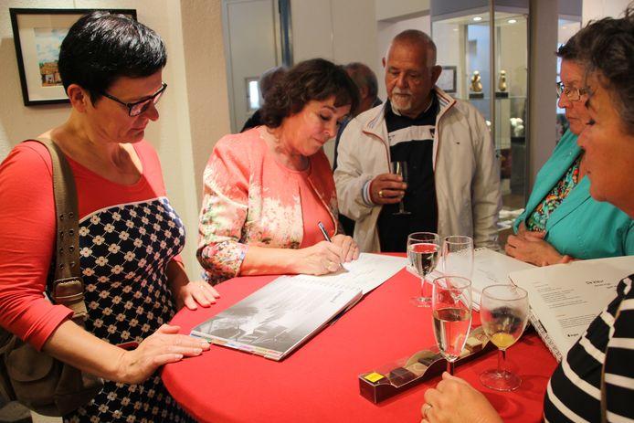 Initiatiefneemster Marie-José Keurlings signeert het herinneringsboek.